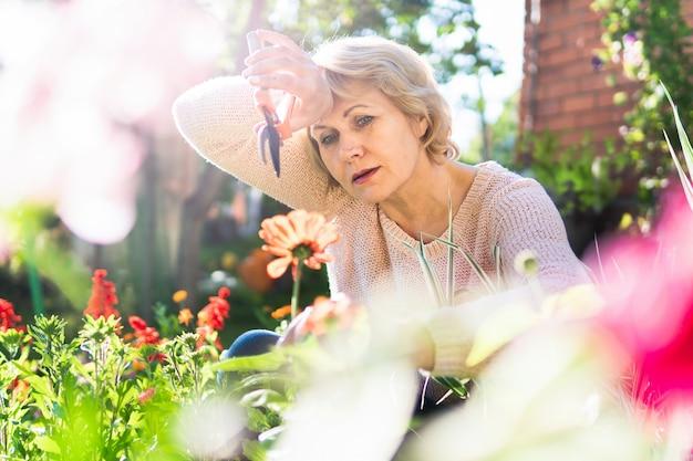 Une femme dans le jardin choisit des fleurs pour les semis. une femme d'âge moyen a un sécateur de jardin. elle travaille au village.