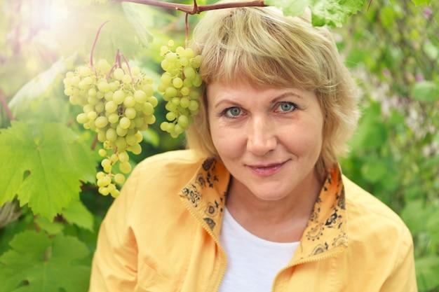 Une femme dans le jardin parmi les buissons de raisin. elle sourit.