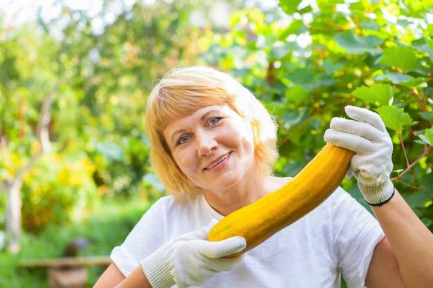 Une femme dans le jardin récolte la courgette de courgette d'automne femme moyenne d'âge