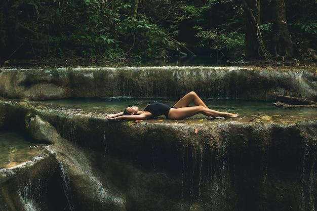Femme dans la jungle avec belle cascade