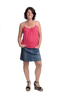 Femme dans une jupe en jean sur un mur blanc avec les mains sur la poche