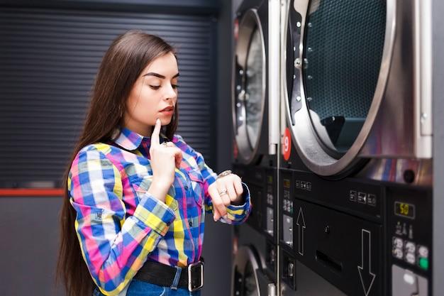 Femme dans la laverie libre-service regarde l'horloge