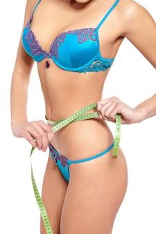 Femme, dans, lingerie bleue, mesurer, forme, isolé, blanc