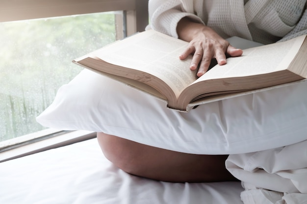 Femme dans le lit et lire un livre.