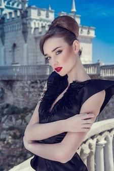Femme dans une longue robe noire sur fond d'un ancien château.