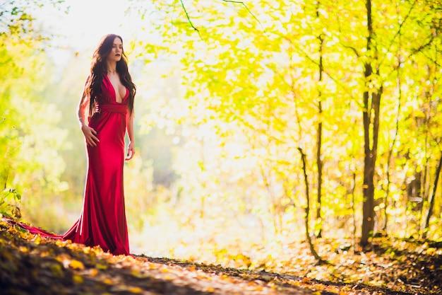 Femme dans une longue robe rouge seule dans la forêt. image fabuleuse et mystérieuse d'une jeune fille dans une forêt sombre au soleil du soir. coucher de soleil, la princesse s'est perdue.
