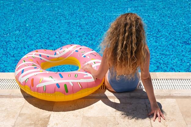 Femme, dans, lunettes soleil, poser, à, gonflable, beignet, piscine