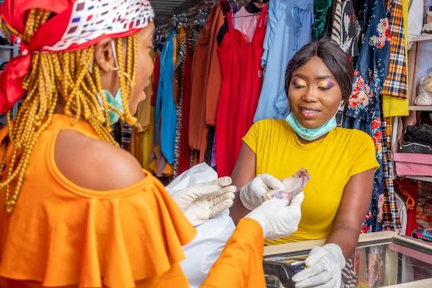 Femme dans un magasin local payant en espèces