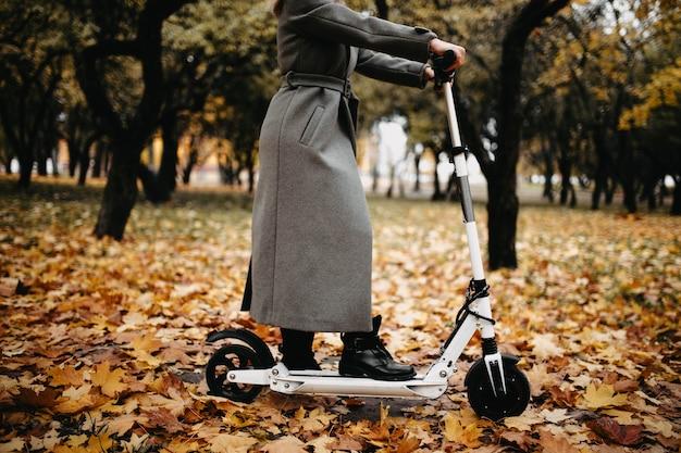 Femme dans un manteau en automne sur un scooter électrique dans un parc d'automne équitation sur des véhicules électriques