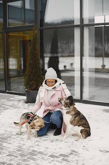 Femme dans un manteau rose avec des chiens
