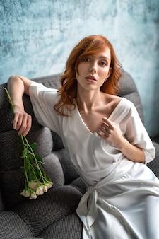 Femme dans un manteau de soie blanc et fleurs. portrait d'une jolie femme