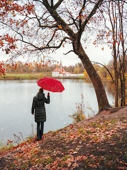 Femme dans un manteau sombre et un parapluie rouge regarde au loin dans un automne enneigé et pluvieux.