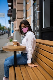 Femme dans un masque médical boit du café dans la rue