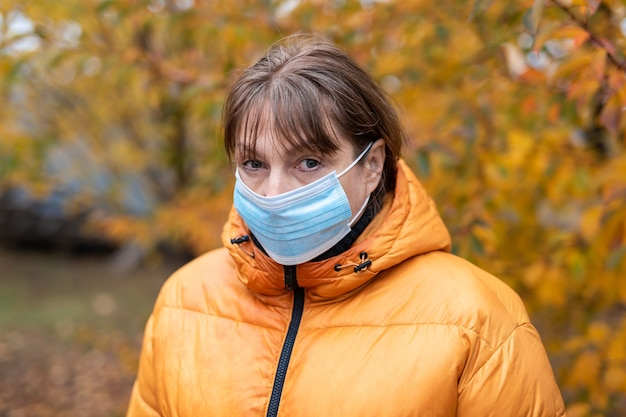 Femme dans un masque médical dans le parc de l'automne