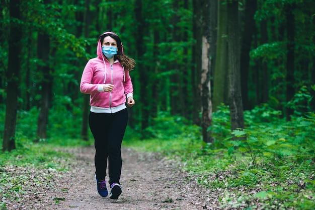 Femme dans un masque médical s'exécute dans la forêt. restez en forme pendant la quarantaine. pandémie de coronavirus covid-19