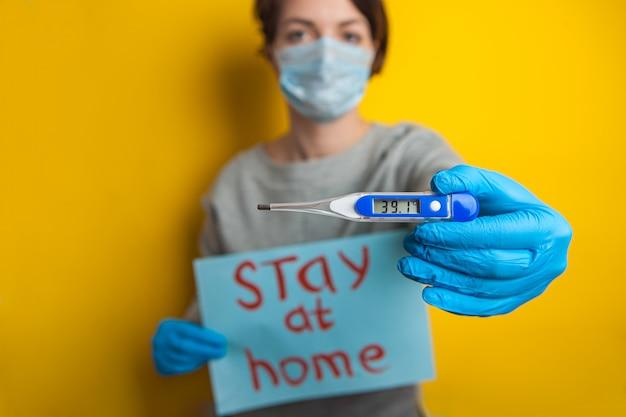 Femme dans un masque médical avec une température. tenant un thermomètre dans ses mains. état bénin d'un patient atteint de coronavirus. rester à la maison