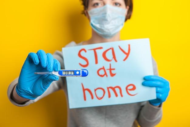 Femme dans un masque médical avec une température. tenant un thermomètre dans ses mains. état bénin d'un patient atteint de coronavirus. restez à la maison jusqu'à l'arrivée du médecin. distribution de covid-19