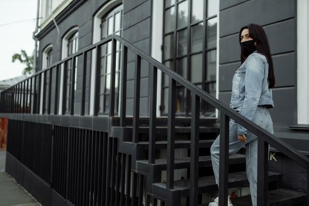 Femme dans un masque de protection sur un balcon regarde une ville vide