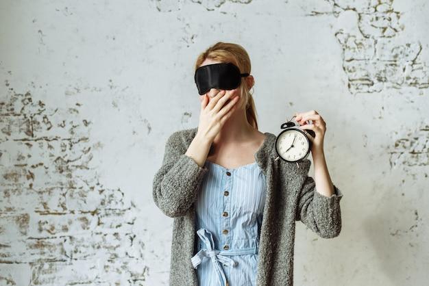 Une femme dans un masque de sommeil tient un réveil dans sa main. elle est fatiguée et paresseuse le matin