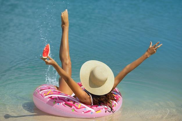 Femme dans la mer sur un anneau en caoutchouc.