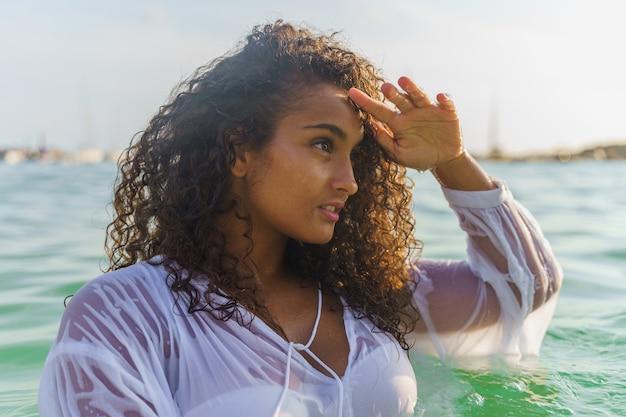 Femme dans la mer regardant l'horizon
