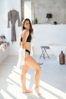 Femme dans le modèle de portrait de mode de salle de bains dans le bain