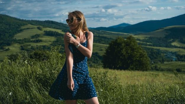 Femme dans les montagnes à l'heure du jour ensoleillé