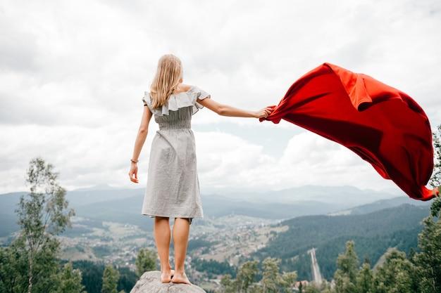 Femme dans les montagnes sauvages donne un signal de détresse sos en utilisant une couverture rouge. concept de situation d'urgence lors d'une randonnée en montagne. femme aux pieds nus se tient à la pierre, agitant une couverture rouge et attendant de l'aide
