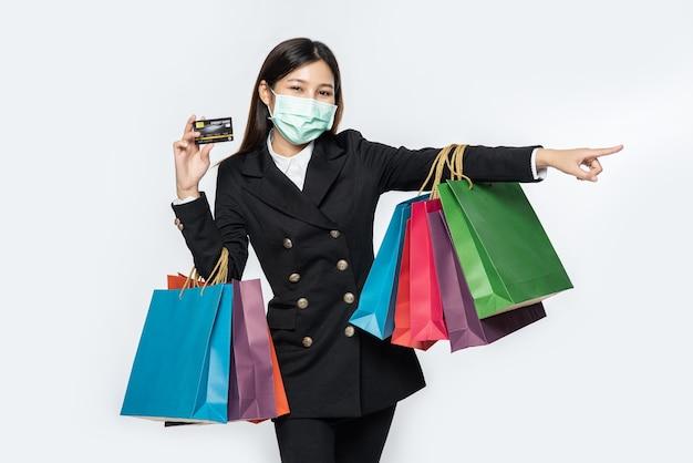 Une femme dans le noir et portant un masque se promène dans les magasins, porte des cartes de crédit et beaucoup de sacs