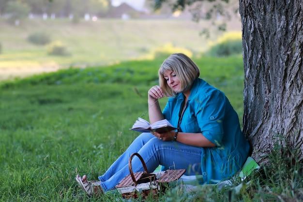Femme dans le parc arbre lecture livre