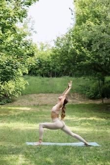 Femme dans le parc d'asanas de yoga sur fond vert d'été