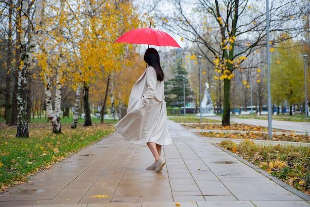 Femme dans le parc dansant sous un parapluie rouge sous la pluie d'automne
