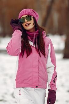 Femme dans un parc d'hiver. dame en combinaison de sport rose. fille dans des lunettes de soleil.