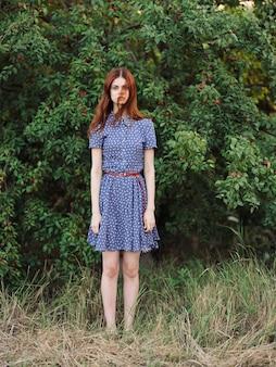 Femme dans le parc près des buissons avec des baies rouges et une robe bleue