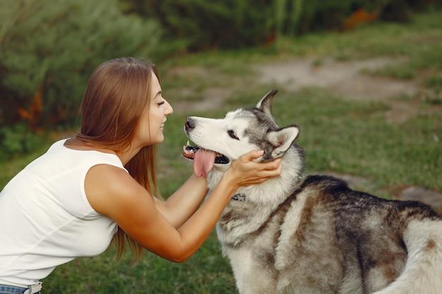 Femme dans un parc de printemps jouant avec un chien mignon