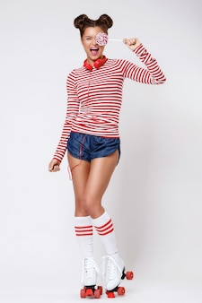 Femme dans les patins à roulettes et avec un casque rouge et une sucette