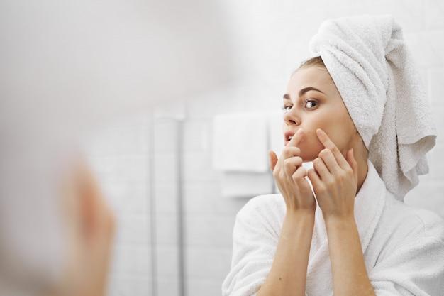 Une femme dans un peignoir dans un peignoir devant un miroir regarde son visage