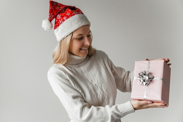 Femme dans un pull blanc et un bonnet de noel rouge tenant un cadeau rose dans ses mains sur fond gris