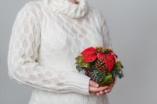 Femme dans un pull blanc tenant une décoration de noël