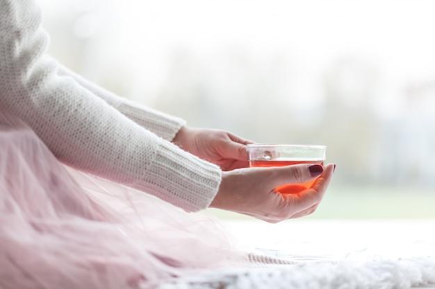 Femme dans un pull gris et des chaussettes chaudes tenant une tasse de thé tout en étant assis sur une couverture tricotée blanche