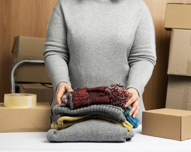 Femme dans un pull gris recueille des vêtements dans une boîte, concept d'assistance et de bénévolat, déménagement. vendre des choses inutiles