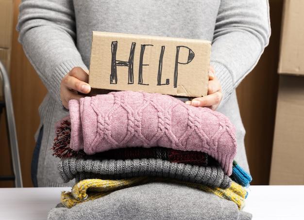 Femme dans un pull gris recueille des vêtements dans une boîte, concept d'assistance et de bénévolat