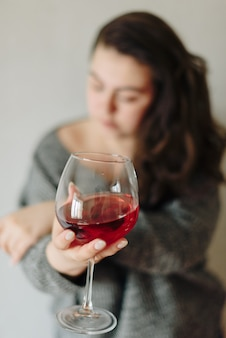 Femme dans un pull gris avec un verre de vin rouge
