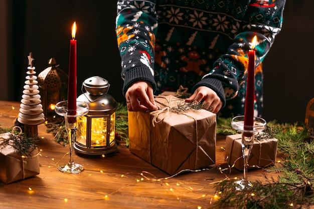 Femme dans un pull de noël attachant une boîte-cadeau artisanale