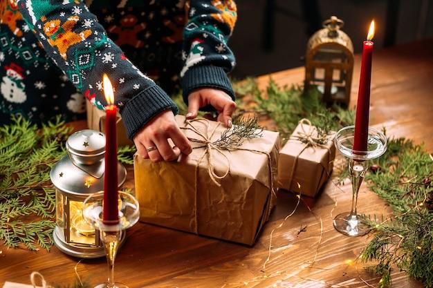 Femme dans un pull de noël tenant une boîte-cadeau artisanale
