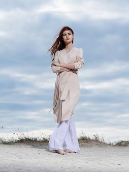 Femme dans un pull et en pantalon blanc sur le sable bleu ciel nuages nature