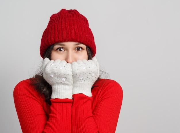 Une femme dans un pull rouge, bonnet tricoté réchauffe son visage avec des mitaines.