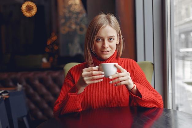 Femme dans un pull rouge. dame boit un café.