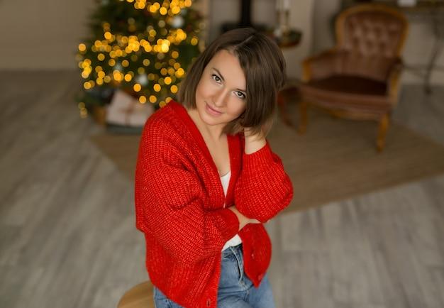 Femme dans un pull rouge dans le contexte d'un arbre de noël.