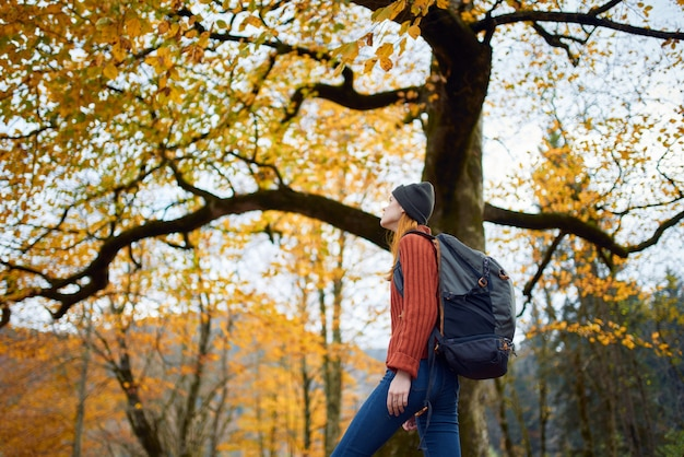 Une femme dans un pull rouge avec un sac à dos se promène dans un parc d'automne dans l'après-midi dans la nature